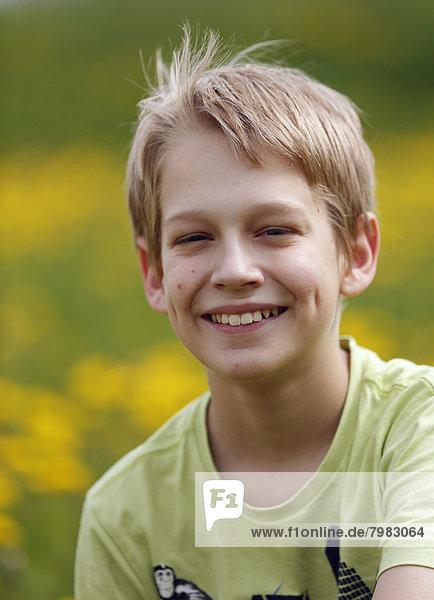Deutschland  Baden Württemberg  Portrait des Jungen auf der Wiese  lächelnd