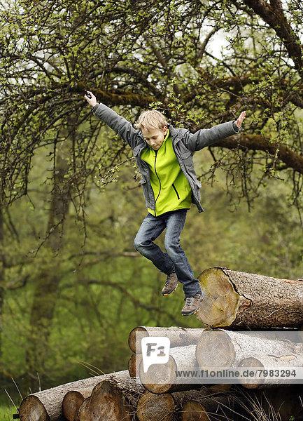 Deutschland  Baden Württemberg  Junge springt aus Holzstämmen