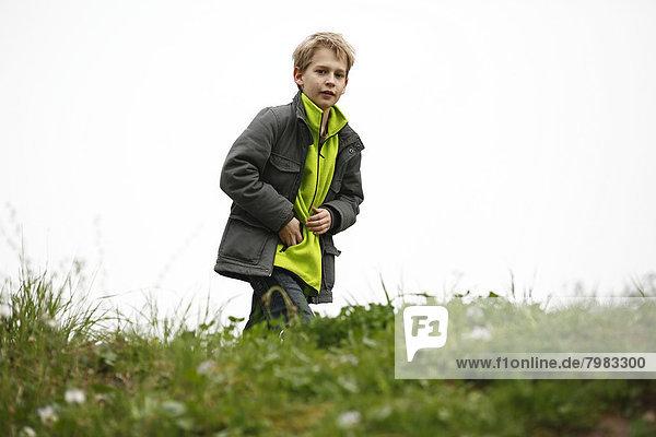 Deutschland  Baden Württemberg  Portrait eines Jungen  der auf der Wiese spazieren geht