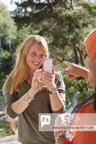 Alvsjo  Sodermanland  Schweden  Frau fotografiert Freundin mit Smartphone