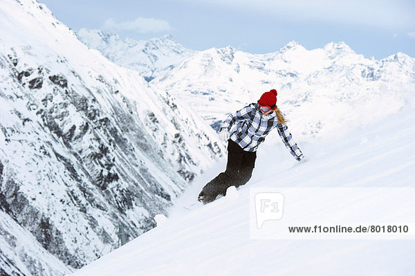 Junge Frau beim Snowboarden