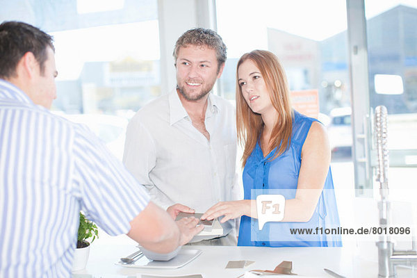 Young couple talking with salesman in kitchen showroom