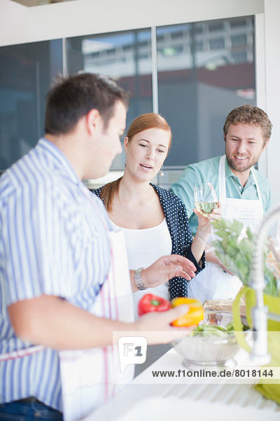 Freunde  die gemeinsam Essen zubereiten