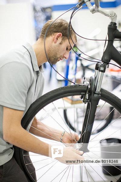 Junger Mann  der auf dem Fahrrad arbeitet
