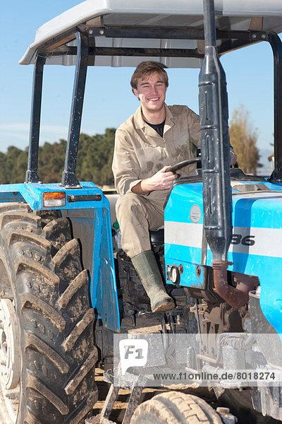 Junger Mann fährt Traktor