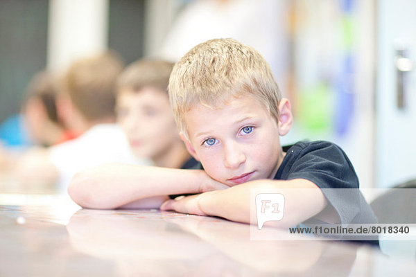 Porträt eines Jungen  der sich auf die Ellenbogen stützt.
