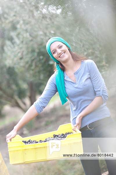 Woman holding crate of olives