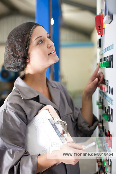 Woman at control panel in olive processing plant