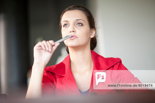 Young woman holding pen looking away