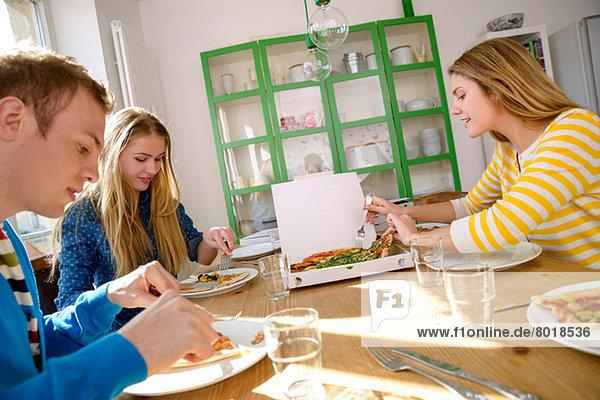 Drei junge Leute essen Pizza