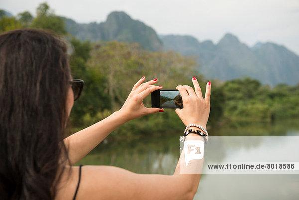 Frau mit Fotohandy  Nam Song River  Vang Vieng  Laos