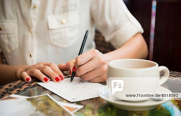 Frau schreibt Postkarte im Café