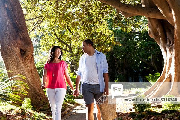 Junges Paar  das auf einem Pfad durch Bäume geht