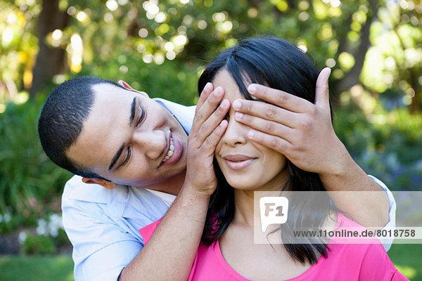 Junger Mann bedeckt das Auge der Frau