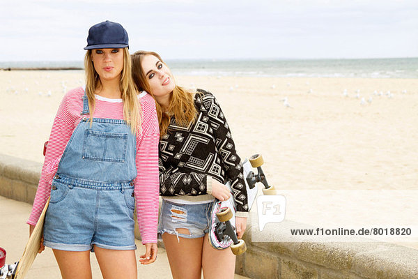Two young women holding skateboards at beach
