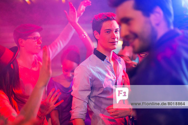 Teenage boy surrounded by group of people dancing at party