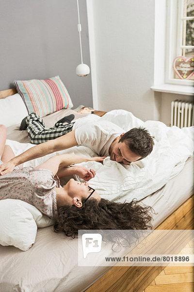 Mittleres erwachsenes Paar im Pyjama auf dem Bett liegend  kitzelnd