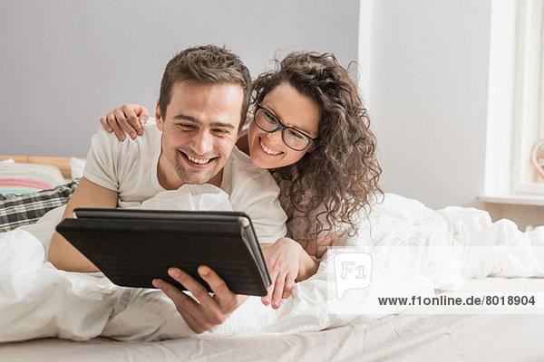 Mittleres erwachsenes Paar auf dem Bett liegend mit Hilfe eines digitalen Tabletts
