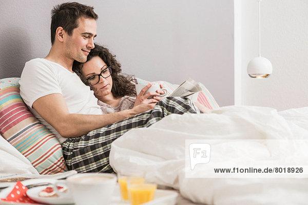 Mittleres erwachsenes Paar liest Zeitung im Bett