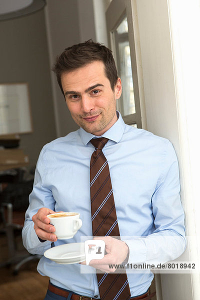 Mature man wearing shirt and tie holding cup of coffee