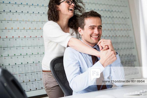 Frau mit Armen um den Hals des Mannes mit Hemd und Krawatte
