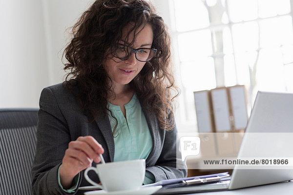 Geschäftsfrau am Schreibtisch mit Laptop und Kaffeetasse