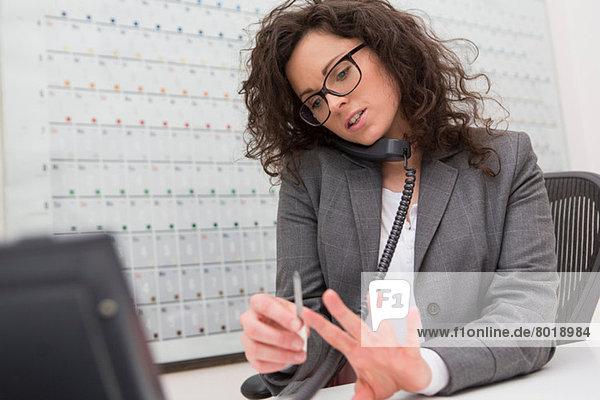 Geschäftsfrau telefoniert  feilt ihre Fingernägel