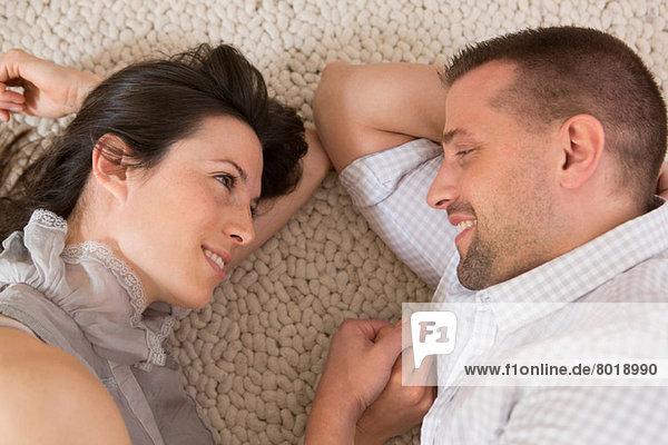 Mittleres erwachsenes Paar auf dem Boden liegend von Angesicht zu Angesicht