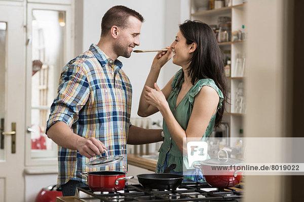 Mittleres erwachsenes Paar kocht Abendessen  Verkostung