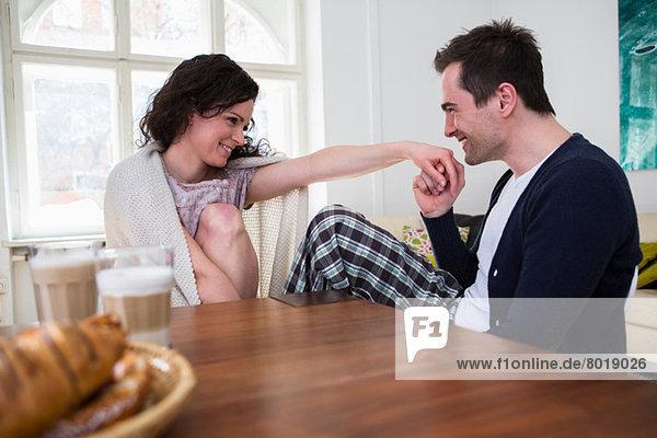 Heterosexuelles Paar am Frühstückstisch Händchen haltend