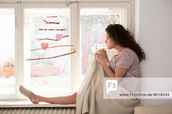 Mid adult woman sat on window seat