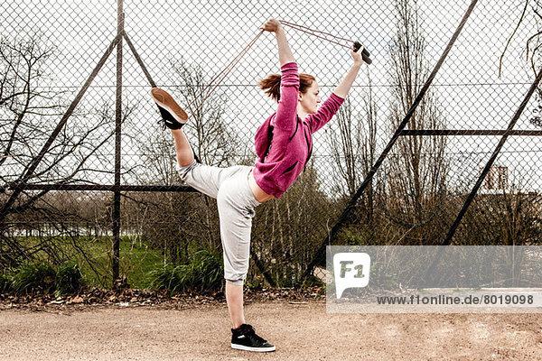 Frau im Kapuzenpulli zieht Pilateseil von hinten gebogenes Bein