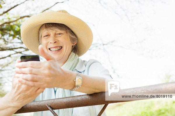 Seniorenfrau lächelt Nachricht auf dem Handy an