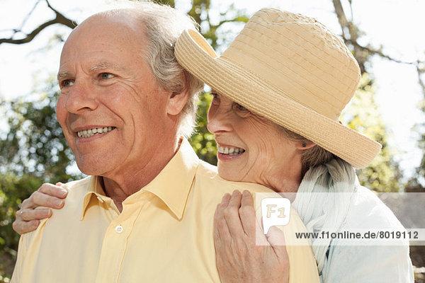 Ehefrau umarmt Mann von hinten