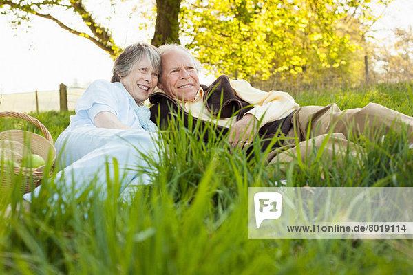 Seniorenpaar beim Entspannen und Picknick auf dem Feld
