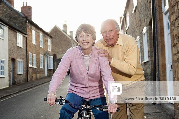 Ehemann unterstützt Frau auf dem Fahrrad