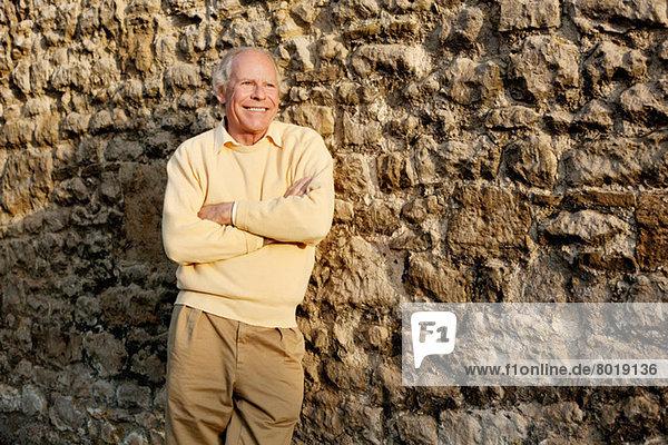 Älterer Mann  der sich mit gekreuzten Armen an die Steinmauer lehnt.