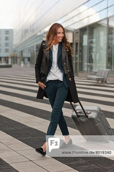 Junge Frau außerhalb des Flughafens mit Trolley-Koffer