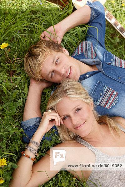 Junges Paar auf Gras liegend mit Blick auf die Kamera