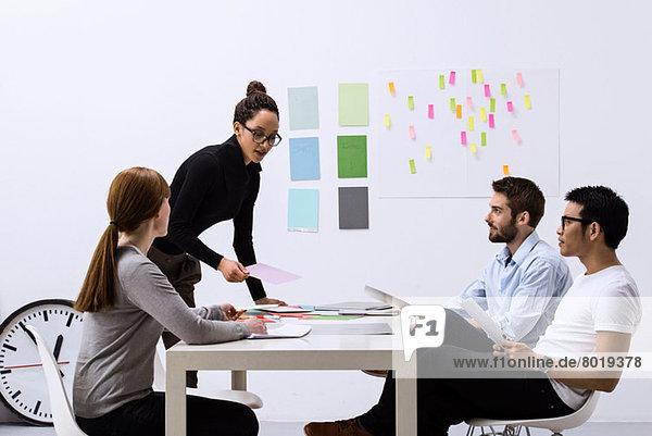 Designteam sitzt am Tisch und diskutiert Ideen
