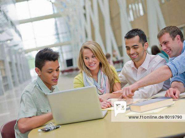 Junger Mann und Studieren mit Tutoren  die auf den Laptop zeigen.