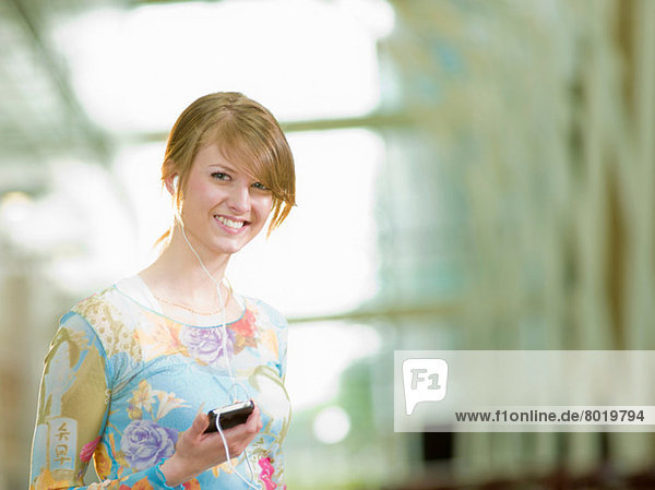 Young woman listening to music with mp3 player  portrait