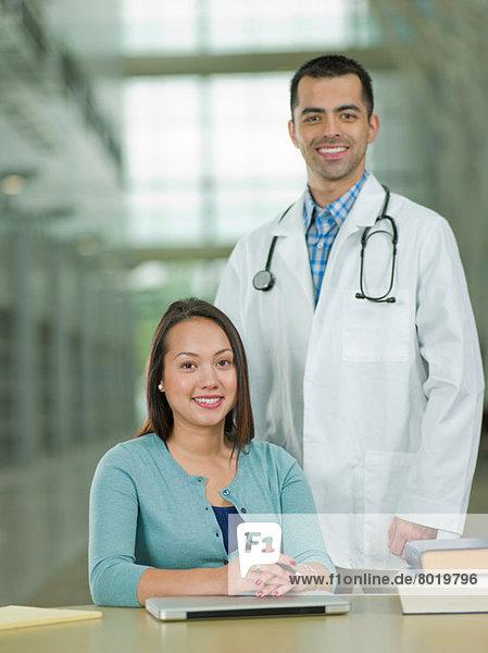 Mittlerer Erwachsener Arzt und junger Student lächelnd  Portrait
