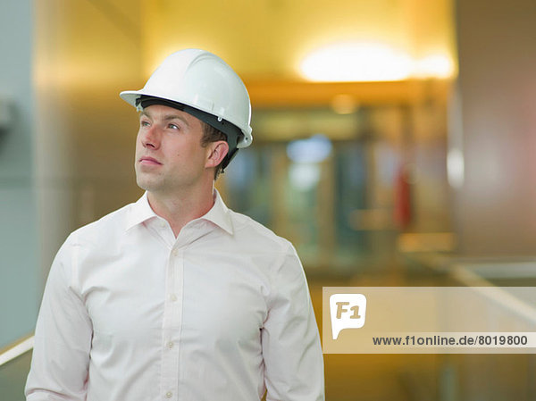 Mid adult construction worker in hard hat  looking up