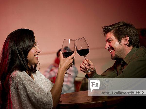 Mittleres erwachsenes Pärchen mit Wein im Restaurant  lächelnd