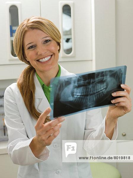 Dentist looking at x-ray  smiling