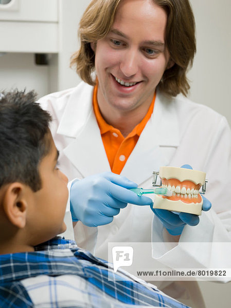 Dentist showing young boy how to brush teeth on model