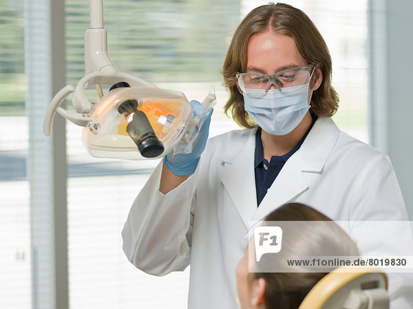 Dentist wearing face mask and using dental camera in examining room