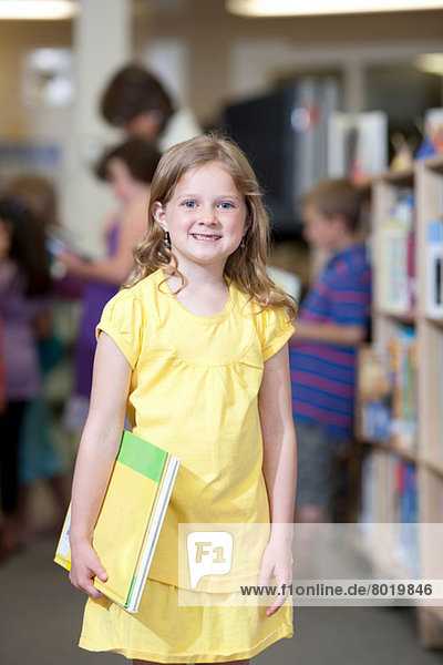 Schoolgirl holding book in library and smiling  portrait