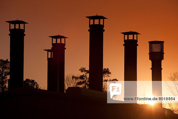 Silhouette of gas pipes in oil refinery at sunset